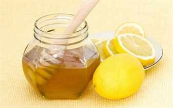 Мед в банке с деревянной ложкой и лимон