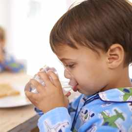 A cute little boy having a drink of water with breakfast