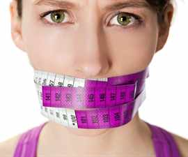 Portrait of a young  woman with a measuring tape covering the mouth