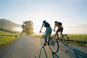 Мужчины едут на велосипеде по дороге