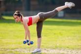 Девушка с гирями делает упражнение