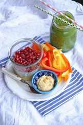 На полосатой скатерти тарелка с овощами и фруктами