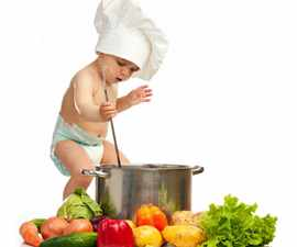 Little boy in chef's hat with ladle, casserole, and vegetables